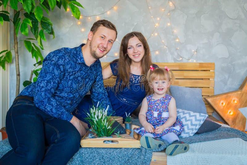 Gelukkige jonge ouders en hun babydochter die togerher spelen royalty-vrije stock foto's