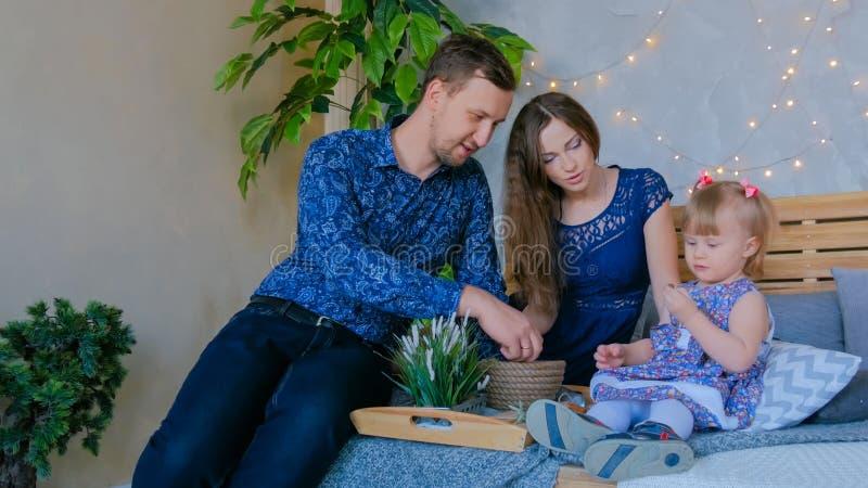 Gelukkige jonge ouders en hun babydochter die togerher spelen stock fotografie