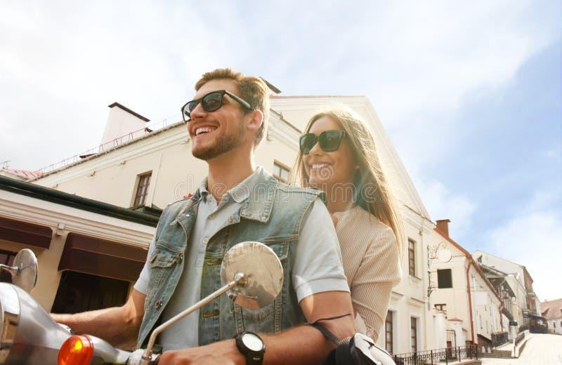 Gelukkige jonge paar berijdende autoped in stad Knappe kerel en jonge vrouwenreis Avontuur en vakantiesconcept stock afbeelding