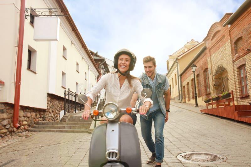Gelukkige jonge paar berijdende autoped in stad Knappe kerel en jonge vrouwenreis Avontuur en vakantiesconcept stock afbeeldingen