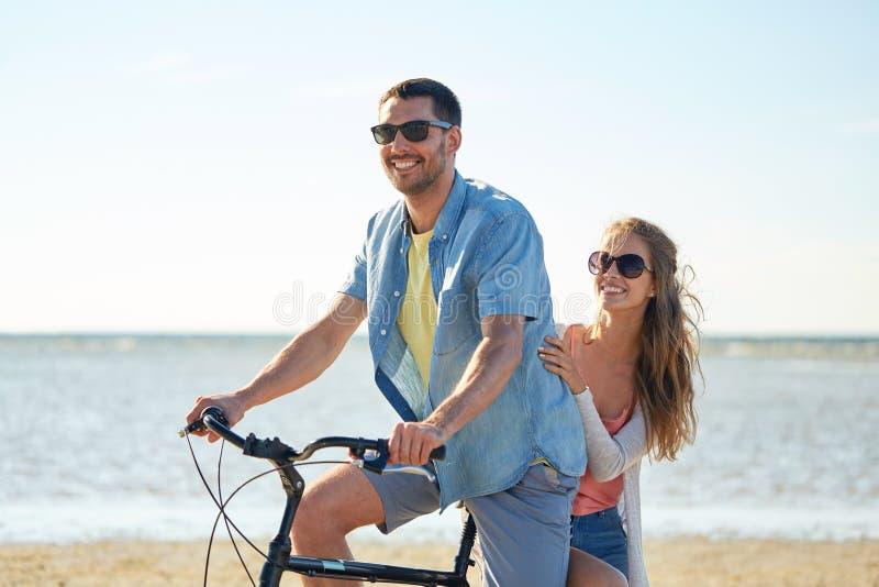 Gelukkige jonge paar berijdende fiets op strand stock foto