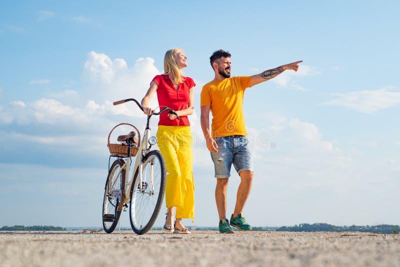 Gelukkige jonge paar berijdende fietsen Pensionering Jonge ruiters die van genieten op reis Tijdens de zomervakantie stock afbeeldingen