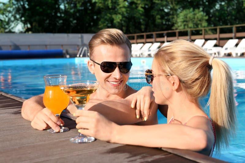Gelukkige jonge paar het drinken cocktails in zwembad bij toevlucht royalty-vrije stock afbeeldingen