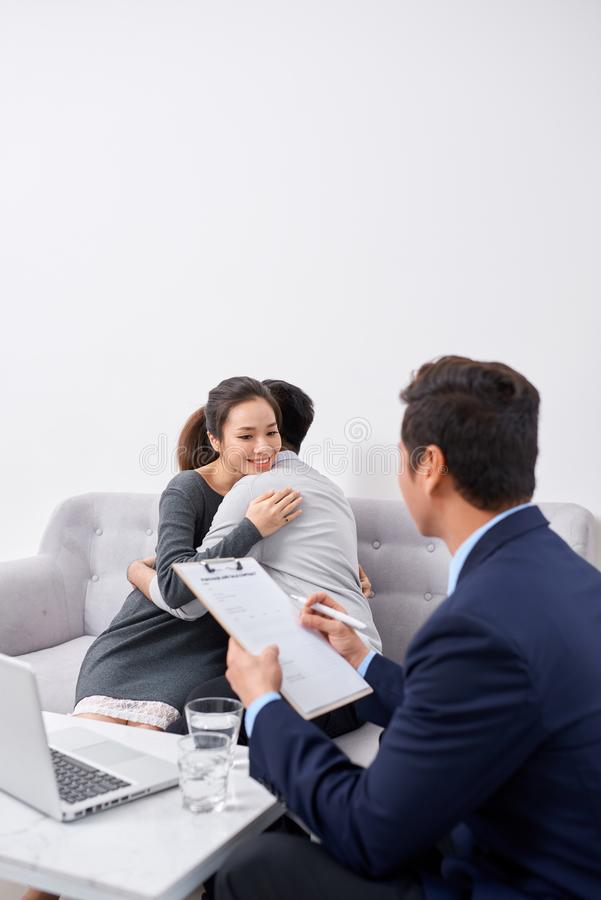 Gelukkige jonge paargreep overhandigt elkaar het luisteren aan vrouwelijke agent, planningshuwelijk, raadplegende beleggingsadvis stock foto's