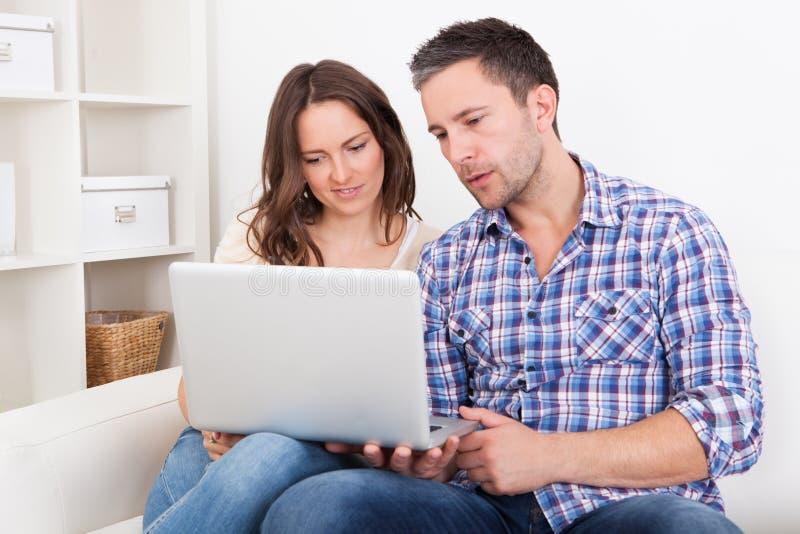 Gelukkige jonge paarzitting op laag die laptop met behulp van royalty-vrije stock fotografie