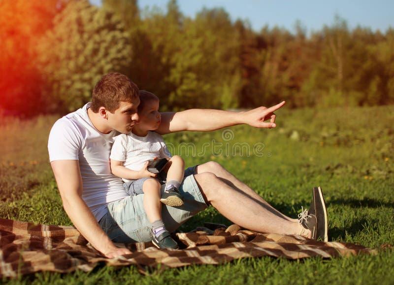 Gelukkige jonge papa en zoon die pret, aard, avond, zonsondergang hebben stock foto's