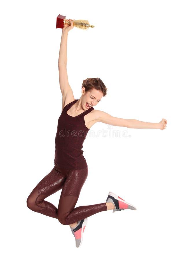 Gelukkige jonge sportvrouw met het gouden trofeekop springen royalty-vrije stock fotografie