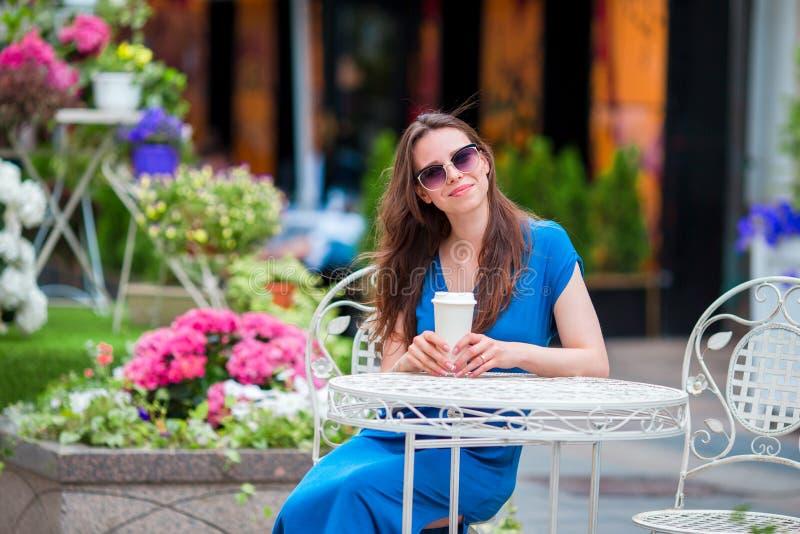 Gelukkige jonge stedelijke vrouw met moderne mobiel en koffie bij openluchtkoffie in Europa De Kaukasische toerist geniet van haa royalty-vrije stock afbeeldingen