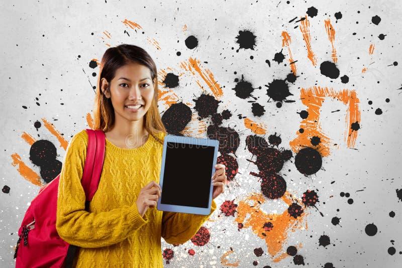Gelukkige jonge studentenvrouw die een tablet houden tegen grijze, gele en zwarte geploeterde achtergrond royalty-vrije stock afbeeldingen