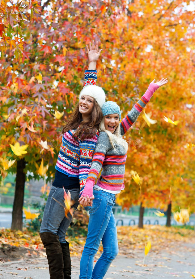 Gelukkige jonge tienermeisjes in de herfstlandschap stock foto