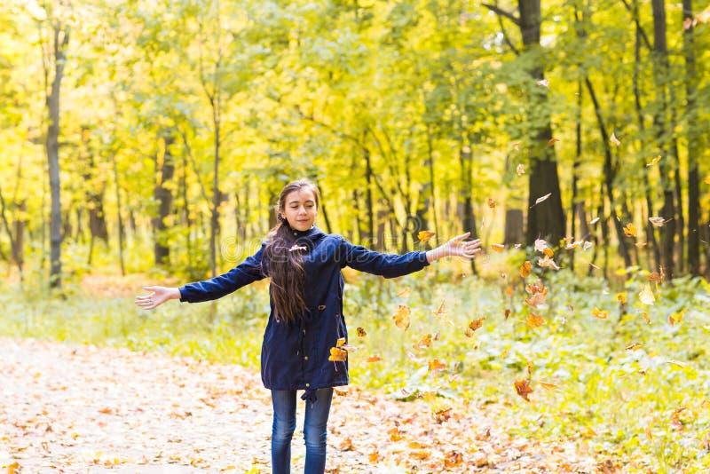 Gelukkige jonge tienermeisjes die in de herfstlandschap bladeren werpen stock foto's