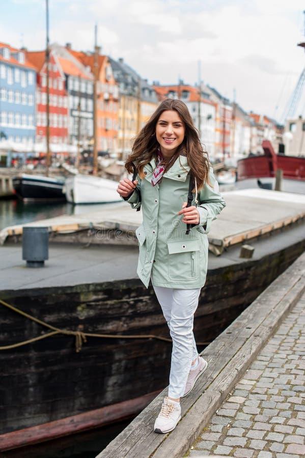 Gelukkige jonge toeristenvrouw met rugzak in Kopenhagen stock fotografie