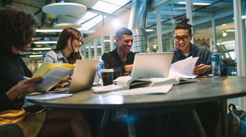 Gelukkige jonge universitaire studenten die met boeken en laptops in bibliotheek bestuderen Groep multiraciale mensen in universi stock foto's