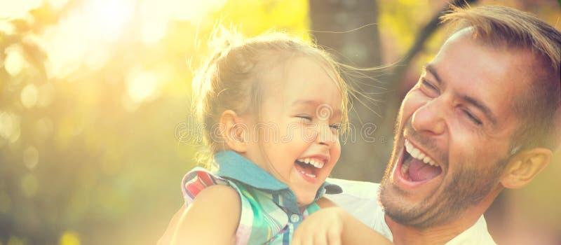 Gelukkige jonge vader met zijn kleine dochter stock afbeelding