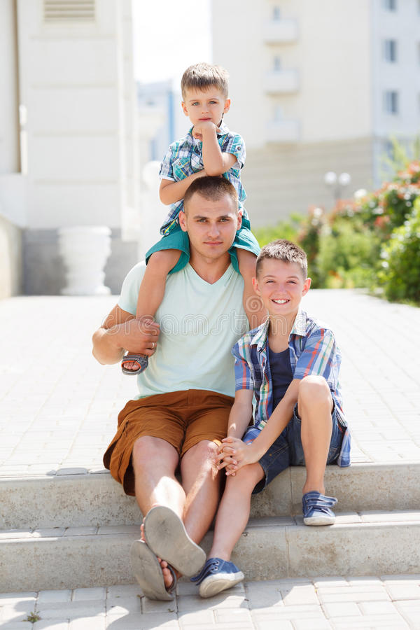 Gelukkige jonge vader met zijn twee zonen stock foto's