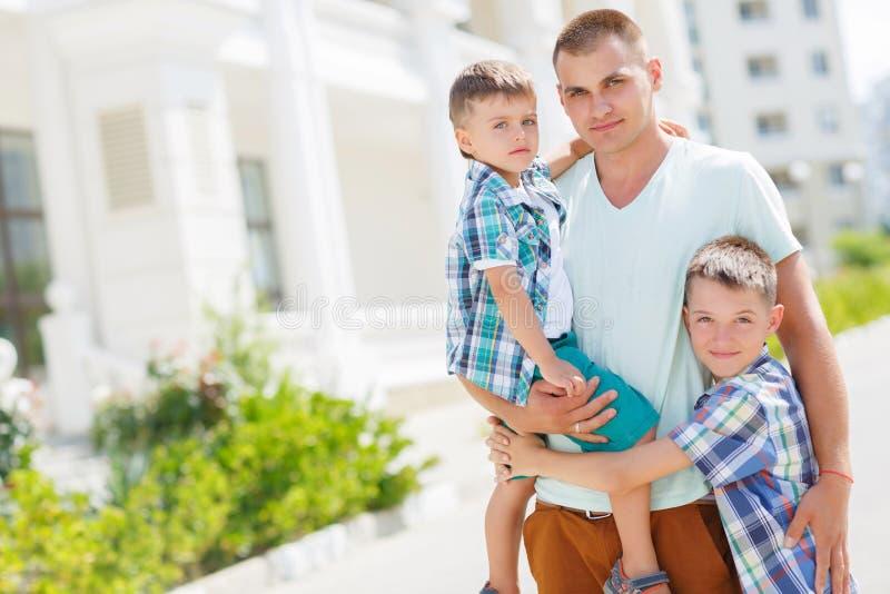 Gelukkige jonge vader met zijn twee zonen royalty-vrije stock foto's