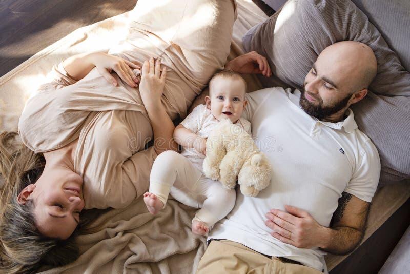 Gelukkige jonge vader, moeder en leuk babymeisje die bij vloer en het ontspannen liggen Het concept van de familie Gebaarde man,  royalty-vrije stock fotografie