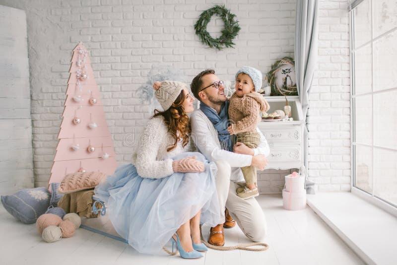 Gelukkige jonge vadermoeder en babyjongen in Kerstmisstudio stock foto