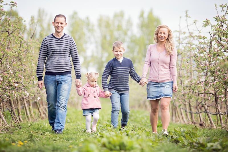 Gelukkige jonge vier lidfamilie die samen in openlucht in orka lopen stock fotografie