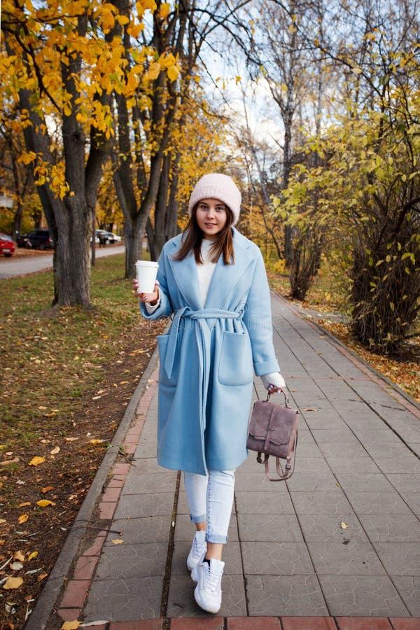 Gelukkige jonge volwassen vrouw die bij de mooie straat lopen die van de de herfststad warme hoed dragen stock afbeeldingen