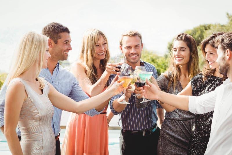 Gelukkige jonge vrienden die dranken hebben royalty-vrije stock afbeeldingen