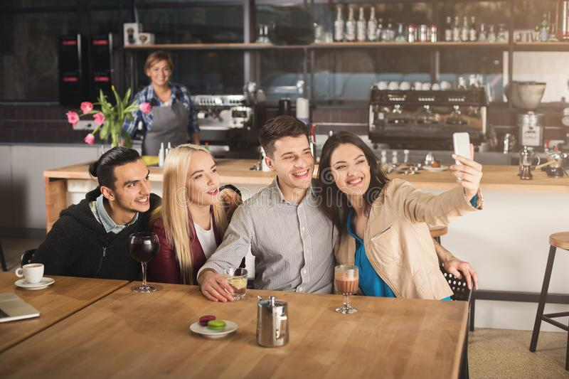 Gelukkige jonge vrienden die koffie drinken bij koffie royalty-vrije stock afbeeldingen