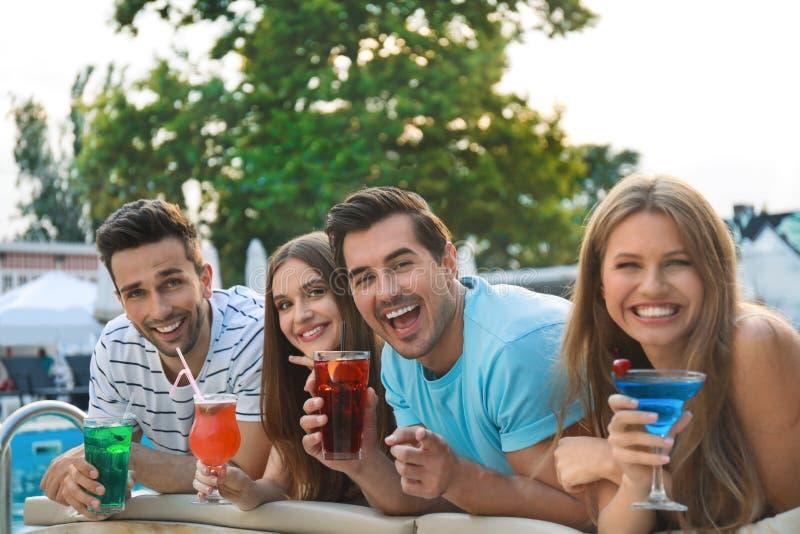 Gelukkige jonge vrienden die met de zomercocktails dichtbij zwembad ontspannen royalty-vrije stock foto's