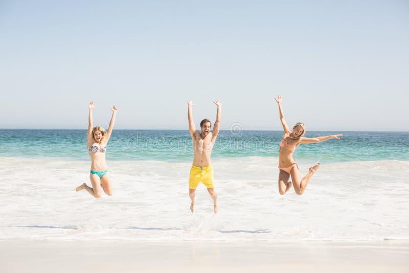 Gelukkige jonge vrienden die op het strand springen royalty-vrije stock fotografie