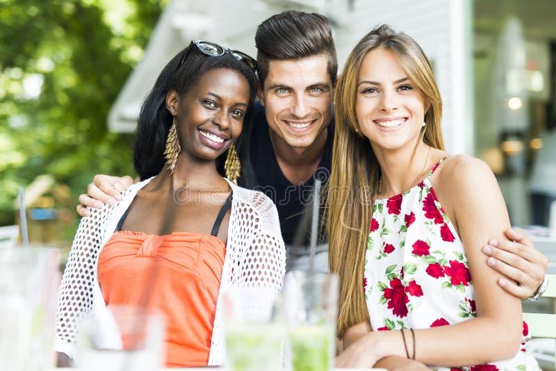 Gelukkige jonge vrienden die in openlucht het zijn dicht bij elkaar glimlachen royalty-vrije stock afbeelding