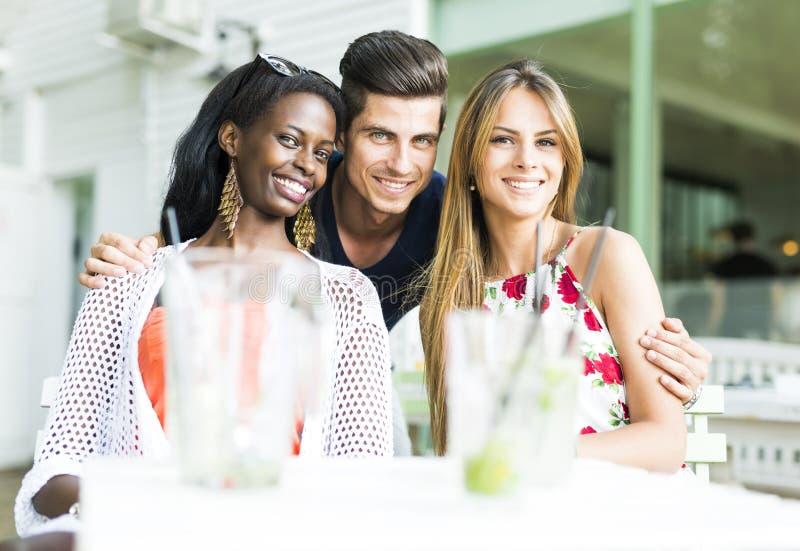 Gelukkige jonge vrienden die in openlucht het zijn dicht bij elkaar glimlachen royalty-vrije stock foto's