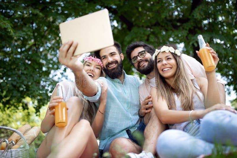 Gelukkige jonge vrienden die pret buiten in aard hebben, die selfie nemen stock foto