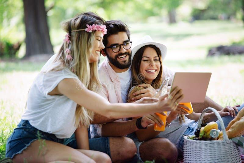 Gelukkige jonge vrienden die pret buiten in aard hebben, die selfie nemen stock fotografie