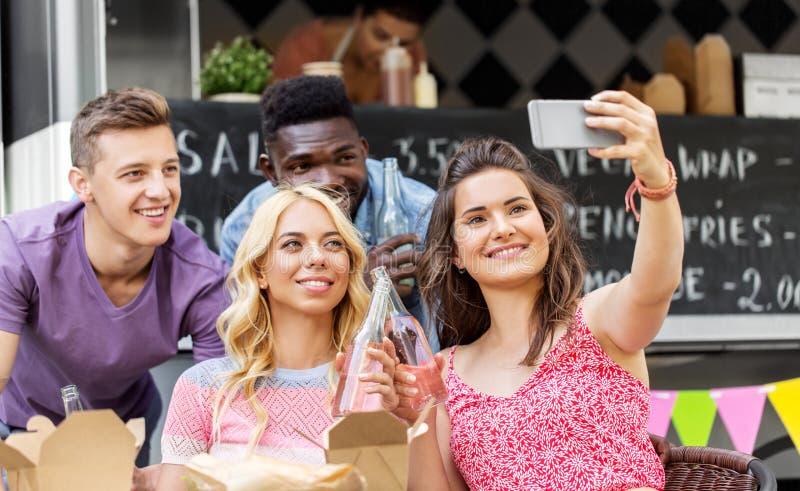 Gelukkige jonge vrienden die selfie bij voedselvrachtwagen nemen stock afbeelding