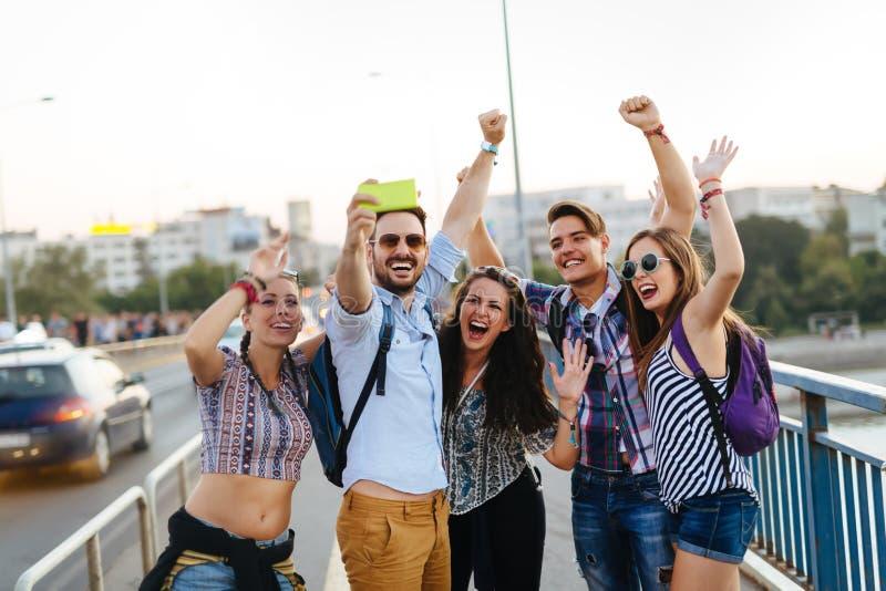 Gelukkige jonge vrienden die selfie op straat nemen stock afbeelding