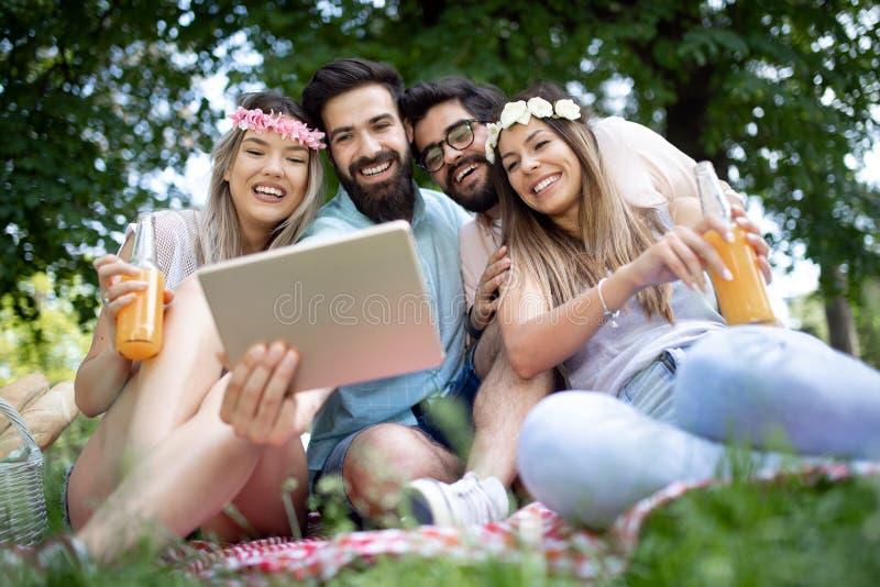 Gelukkige jonge vrienden die selfies op een picknick nemen openlucht stock afbeeldingen