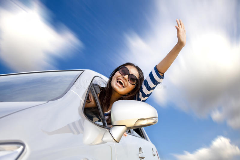 Gelukkige jonge vrouw in auto het drijven stock afbeelding