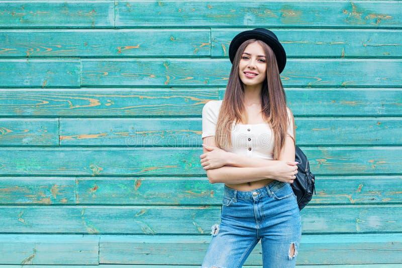 Gelukkige jonge vrouw in blauw denim op houten achtergrond in openlucht stock foto