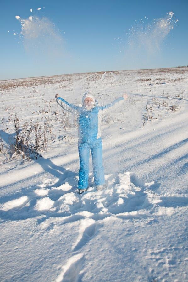Gelukkige jonge vrouw in blauw skikostuum op sneeuw royalty-vrije stock afbeelding