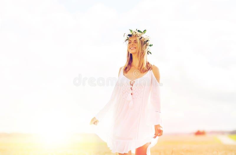 Gelukkige jonge vrouw in bloemkroon op graangewassengebied stock afbeeldingen