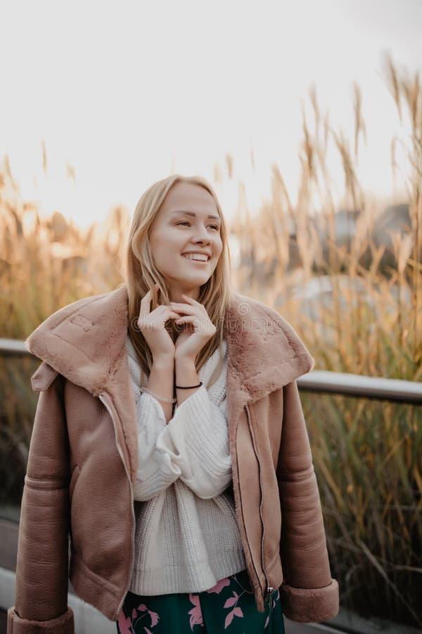 Gelukkige jonge vrouw in de herfstseizoen op een stadsstraat op zonsopgang royalty-vrije stock foto