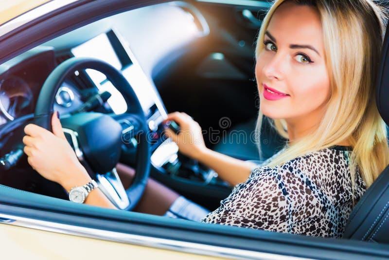 Gelukkige jonge vrouw in de moderne luxeauto stock afbeelding
