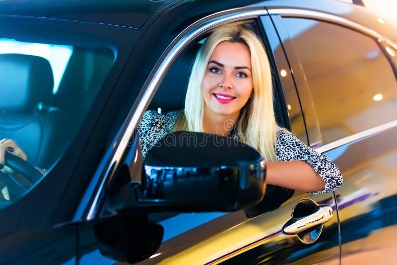 Gelukkige jonge vrouw in de moderne luxeauto royalty-vrije stock afbeelding