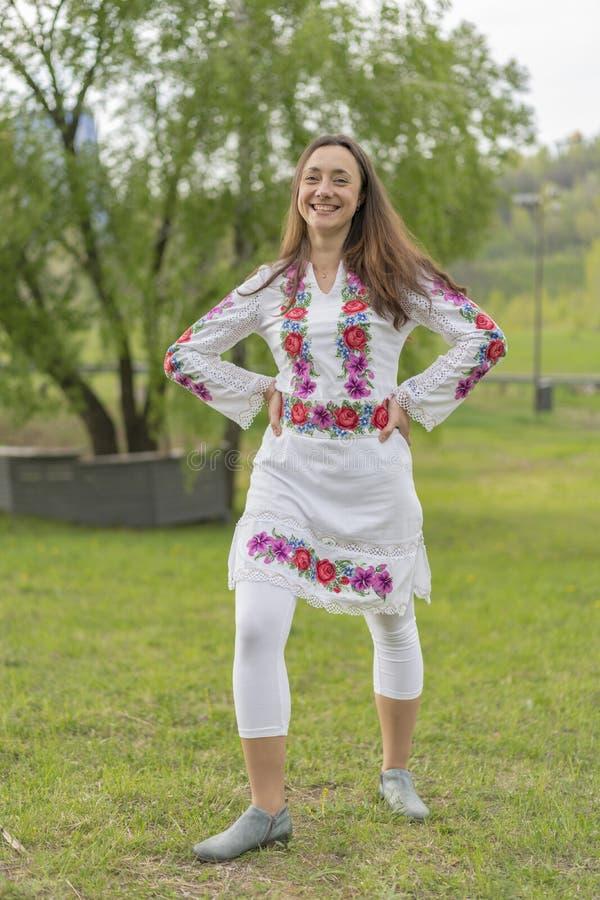 Gelukkige jonge vrouw in de Oekraïense nationale kleren in het park Vrouw in borduurwerk Verticale foto royalty-vrije stock fotografie