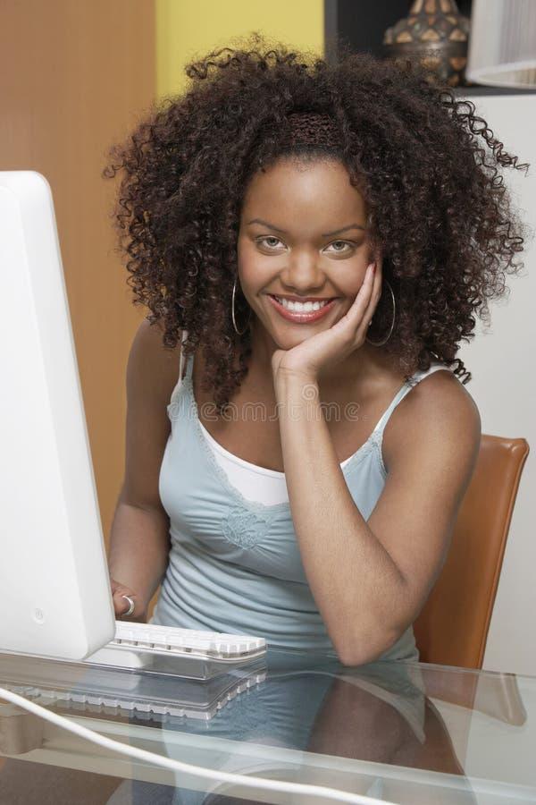 Gelukkige Jonge Vrouw die aan Computer werken stock foto