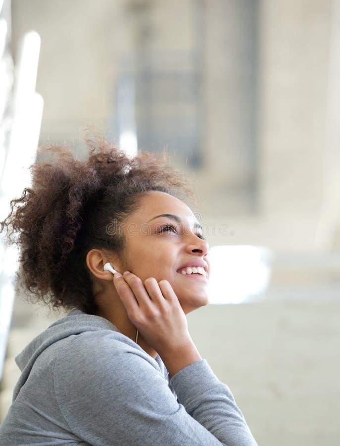 Gelukkige jonge vrouw die aan muziek met oortelefoons luisteren stock fotografie