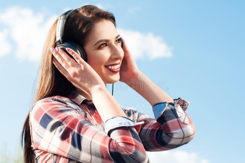 Gelukkige jonge vrouw die aan muziek onder de blauwe hemel luisteren stock fotografie