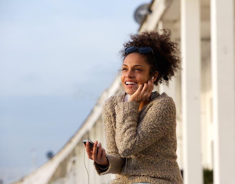 Gelukkige jonge vrouw die aan muziek op mobiele telefoon luistert royalty-vrije stock afbeeldingen