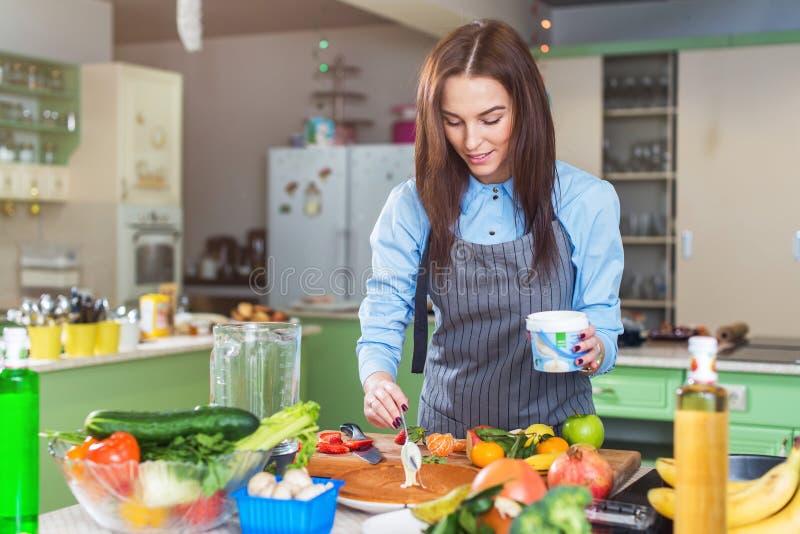 Gelukkige jonge vrouw die cake maken die een laag met room smeren die zich in keuken bevinden royalty-vrije stock afbeelding