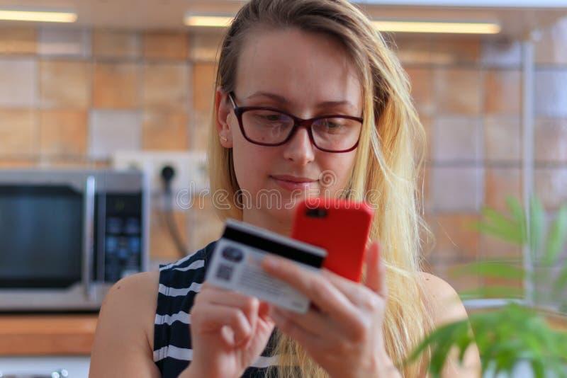 Gelukkige jonge vrouw die creditcard en telefoon in keuken thuis met behulp van stock afbeelding
