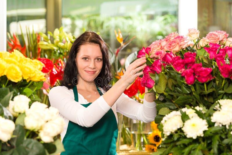 Gelukkige jonge vrouw die de winkel van de bloemenbloemist schikken stock afbeeldingen